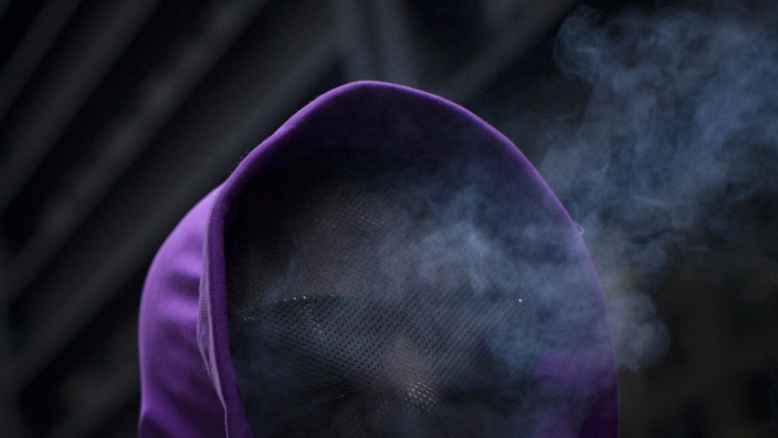 Cigarette smoke rises from the hooded face of an Occupy Wall Street activist as he takes part in a protest through New York