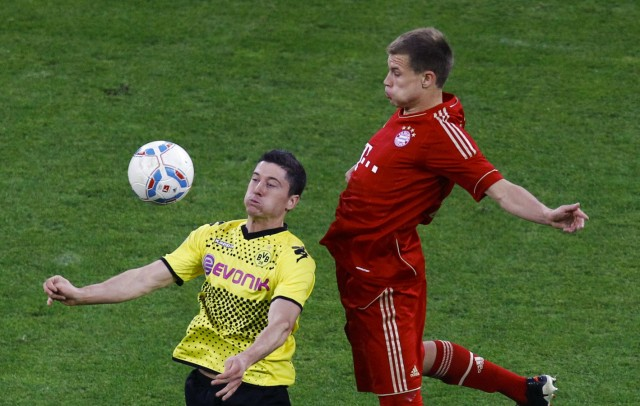 Lewandowski of Borussia Dortmund challenges Badstuber of Bayern Munich during their German first division Bundesliga soccer match in Dortmund
