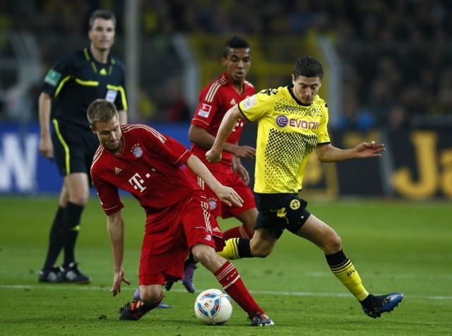Lewandowski of Borussia Dortmund challenges Badstuber of Bayern Munich during their German first division Bundesliga soccer match in Dortmund