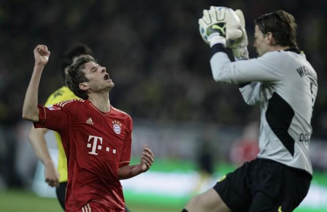 Bayern Munich's Mueller reacts as Borussia Dortmund's goalkeeper Weidenfeller catches the ball during their German first division Bundesliga soccer match in Dortmund