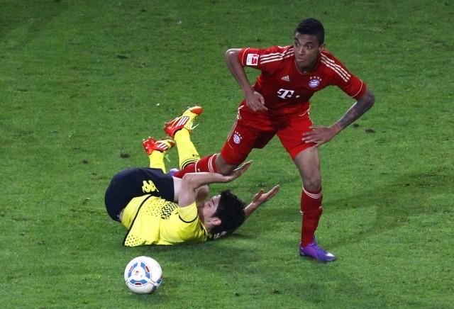 Gustavo (R) of Bayern Munich tackles  Kagawa of Borussia Dortmund during their German first division Bundesliga soccer match in Dortmund