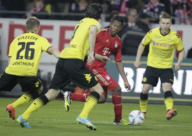 Bayern Munich's Alaba is tackled by Borussia Dortmund's Subotic and Pisczek during their German first division Bundesliga soccer match in Dortmund