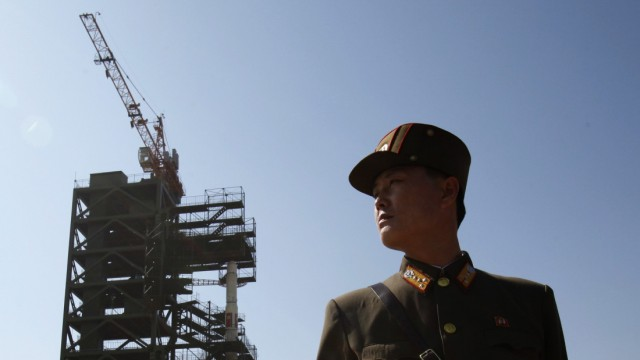 File photo of a soldier standing guard in front of the Unha-3 (Milky Way 3) rocket sitting on a launch pad at the West Sea Satellite Launch Site in the northwest of Pyongyang