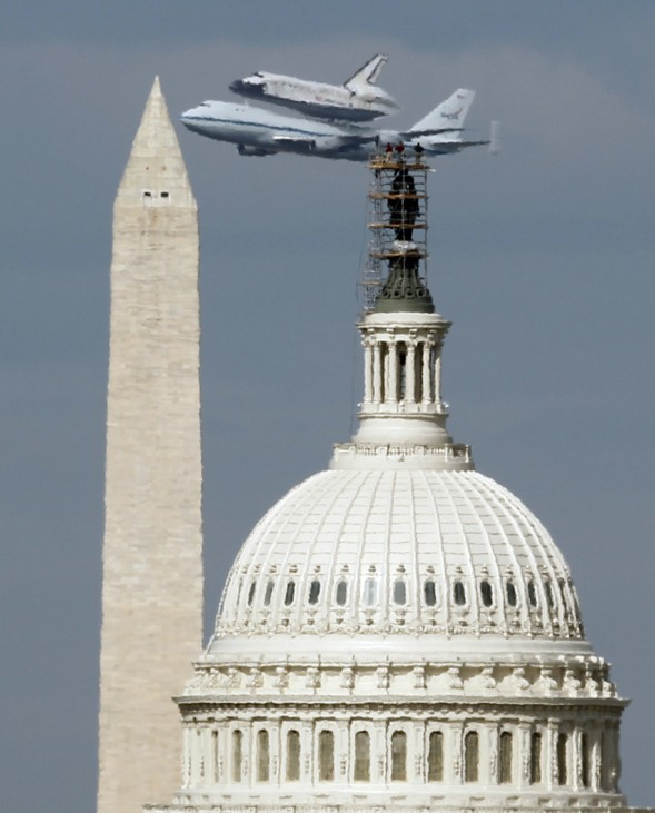 Space Shuttle Discovery passes the Washington Monument and the U.S. Capitol atop a NASA modified 747 plane in Washington