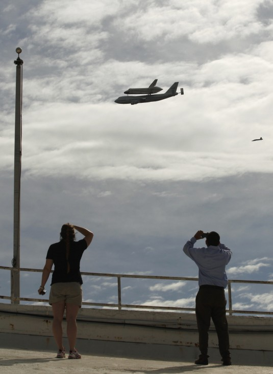 People look up from the rooftop of RFK Stadium in Washington to see the Space Shuttle Discovery fly past