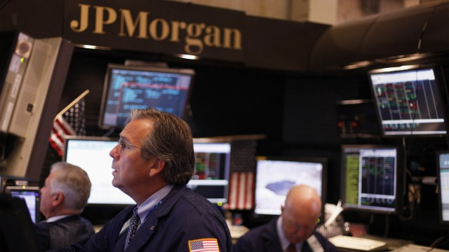 Traders work in the JP Morgan company stall on the floor of the New York Stock Exchange in New York