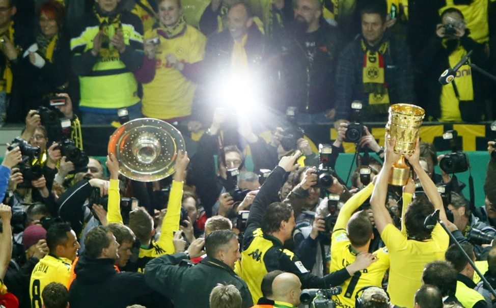 Borussia Dortmund players celebrate with German soccer championship trophy and DFB Cup trophy after DFB Cup final in Berlin