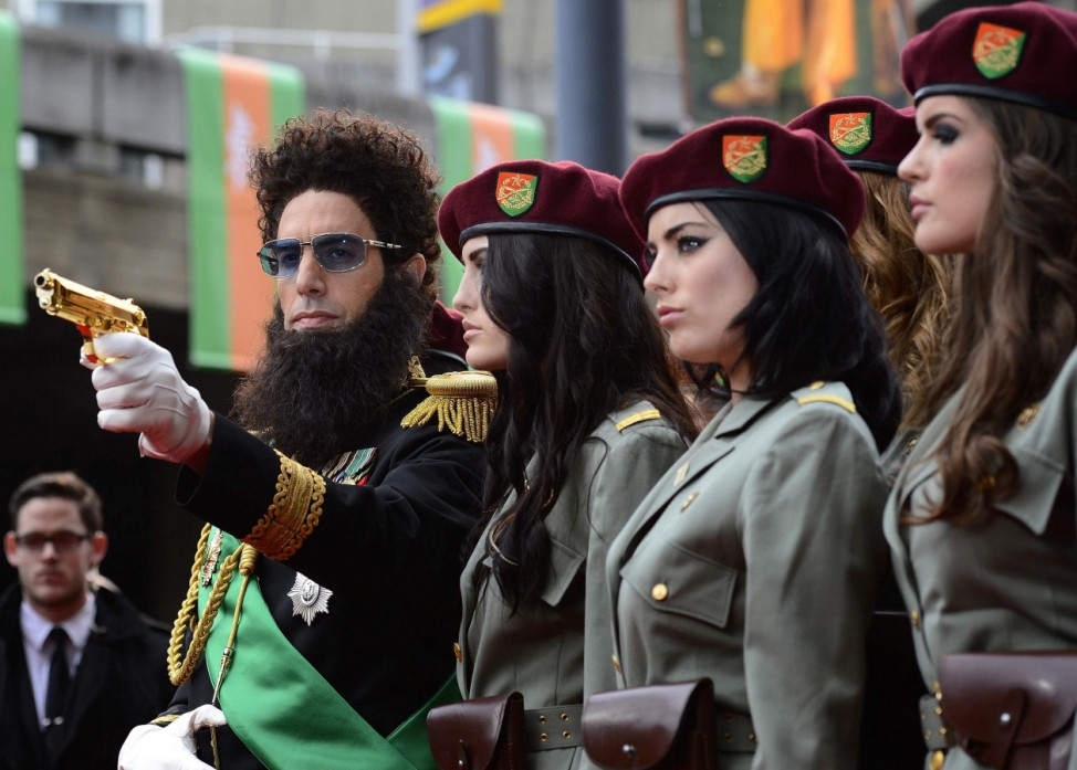 Actor Sacha Baron Cohen points a gun as he poses with models at the world premiere of the Dictator at the Royal Festival Hall in London