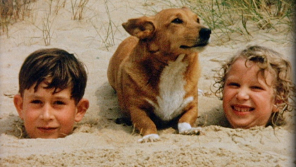 In this undated handout photo provided by Clarence House, Prince Charles (L) and Princess Anne play in the sand with a corgi at Holkham Beach, 1957