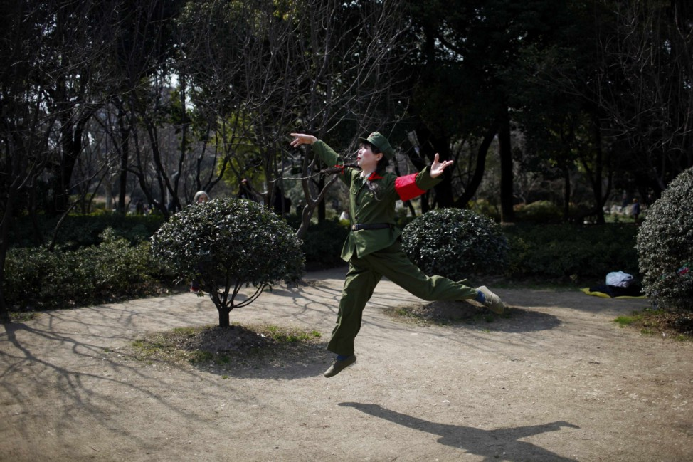 Xiao Cao performs as a cultural revolution red guard at a park in Shanghai