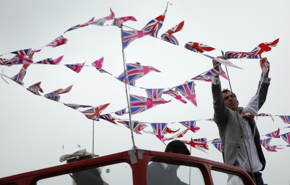 A racegoer strings bunting to the top of a double decker bus at the Epsom Derby festival in Epsom, southwest of London