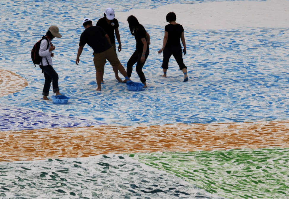 Participants use their feet to paint a 1,600-square-metre painting during a charity event to raise funds for the mentally disabled in Hong Kong