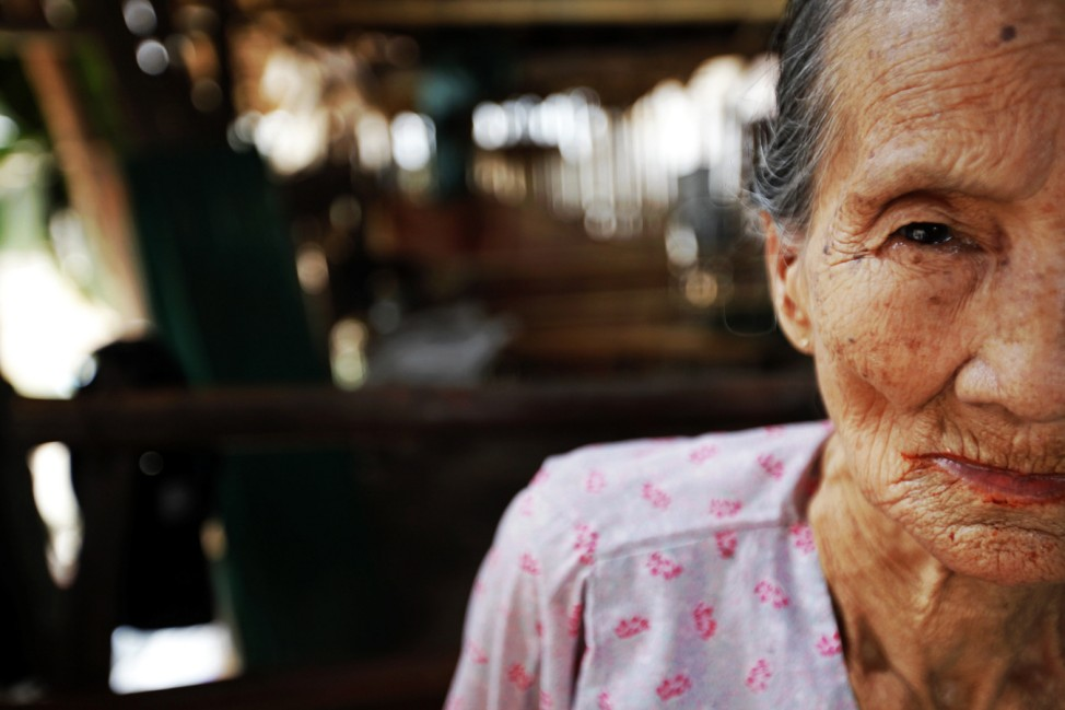 Munane, 90 year old ethnic Karen refugee who begs for rice for herself and her disabled granddaughter after her parents died sits inside a home at the Mae La refugee camp near Mae Sot