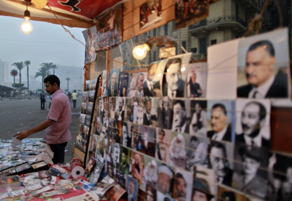 Vendor stands next to pictures of Arab leaders at his stall, during sit-in at Tahrir Square after court sentenced deposed president Mubarak to life in prison in Cairo