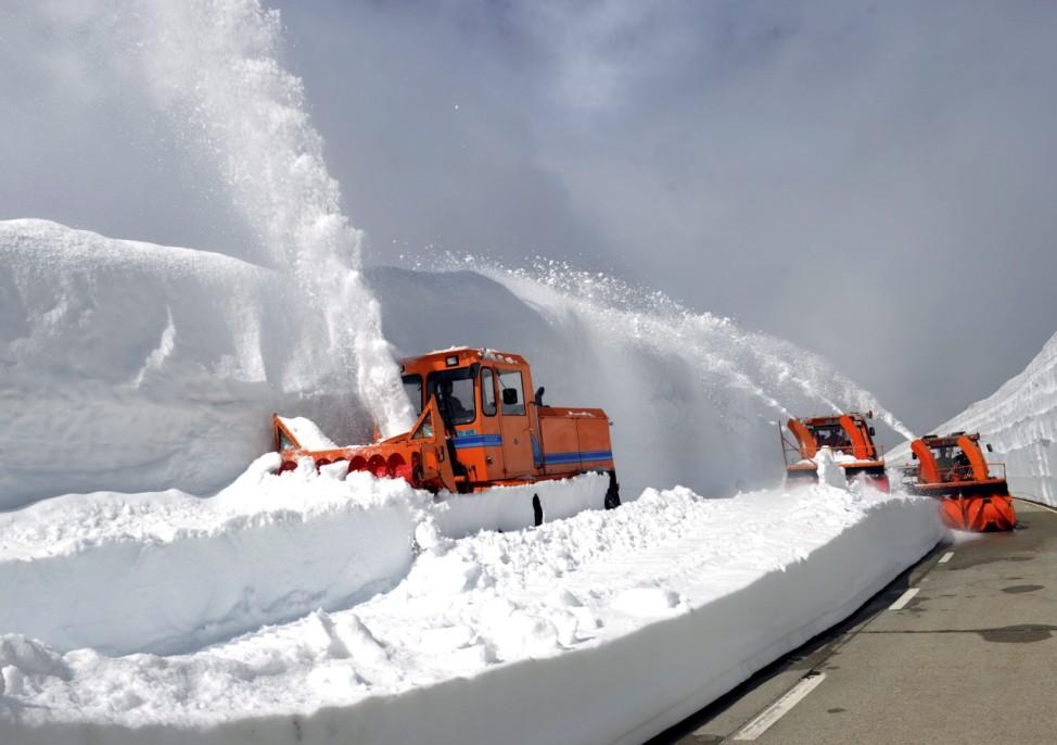Snow plow trucks clear the street on the mountain pass Nufenen