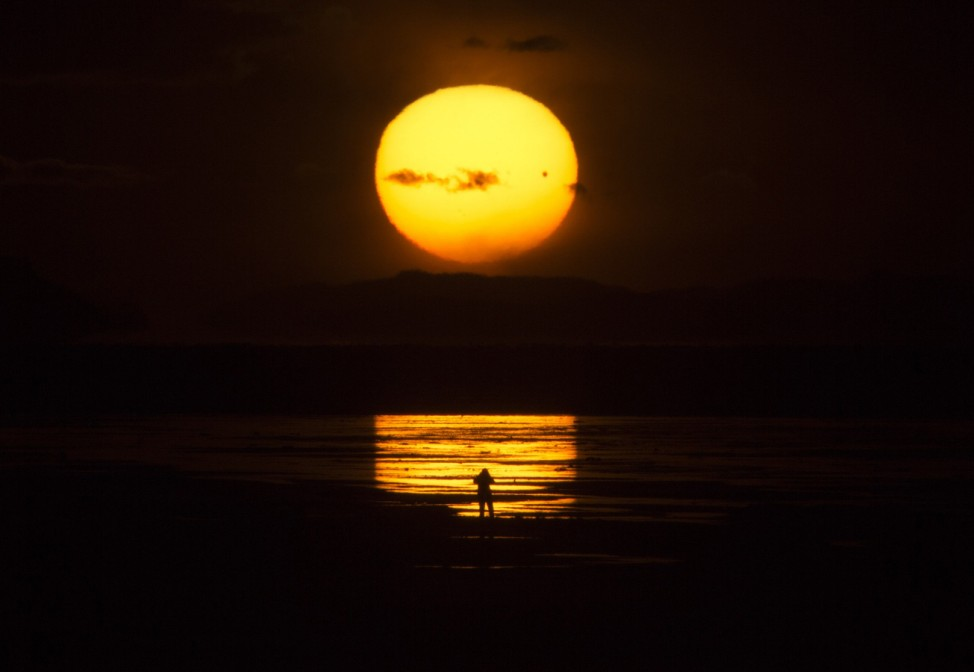 The planet Venus makes a transit as a person watches the sun set over the Great Salt Lake outside Salt Lake City