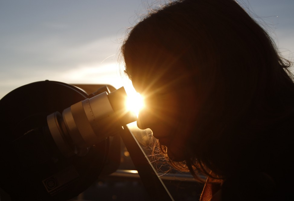 A woman looks through a telescope as the planet Venus transits across the sun during sunrise in Vienna