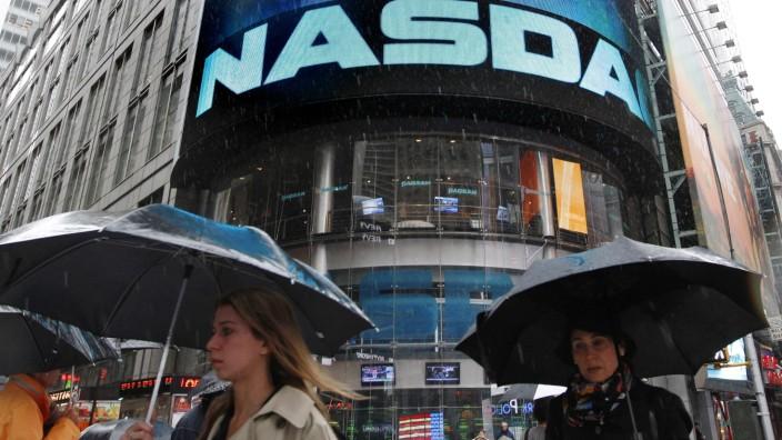 Commuters pass by the NASDAQ Marketsite in New York