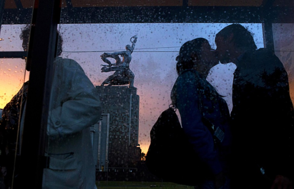 A couple kiss at a tram stop in front of the soviet era statue 'Worker and Kolkhoz woman' near Moscow's All Russia Exhibition Centre
