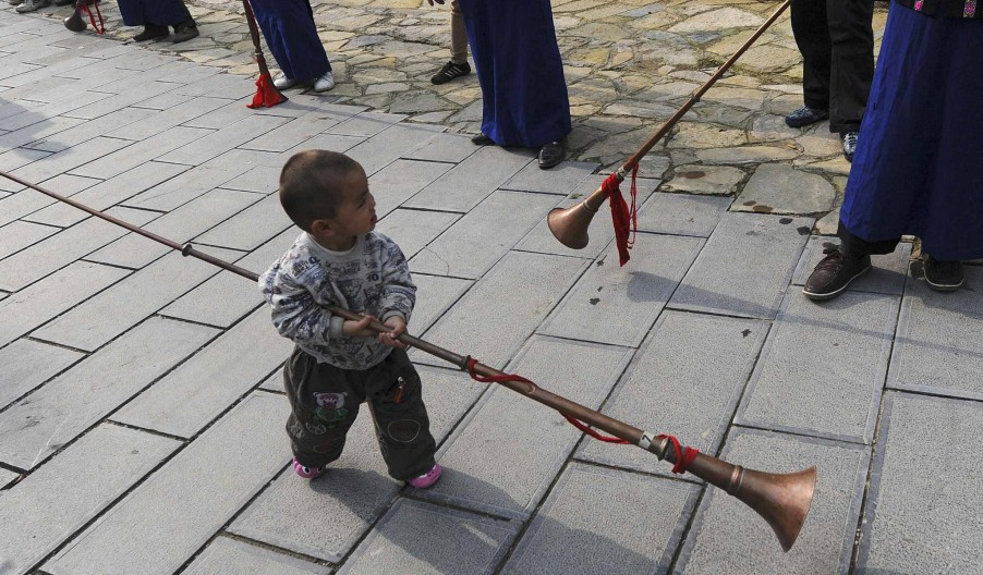 A child carries a suona as he walks past a receiving line for greeting visitors at Pianpo Village in Kai county, Guizhou province