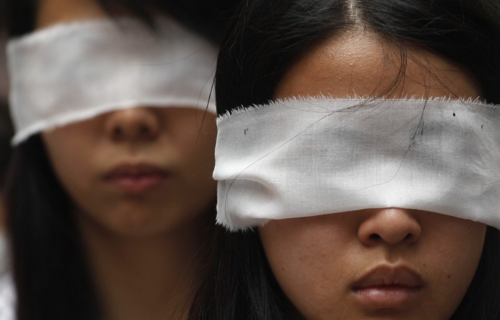 Protesters cover their eyes with white ribbons to symbolize mourning to urge Chinese authorities to carry out proper investigation into death of dissident Li in Hong Kong
