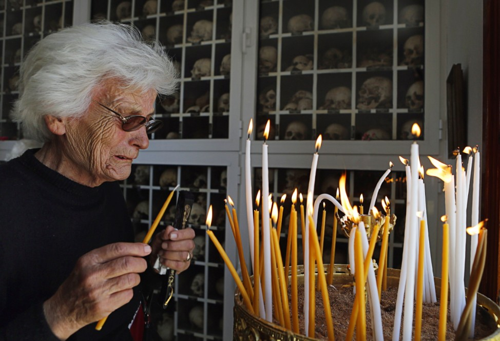 Mario weeps as she lights candle inside mausoleum during 68th anniversary of Nazi wartime Distomo massacre in village of Distomo