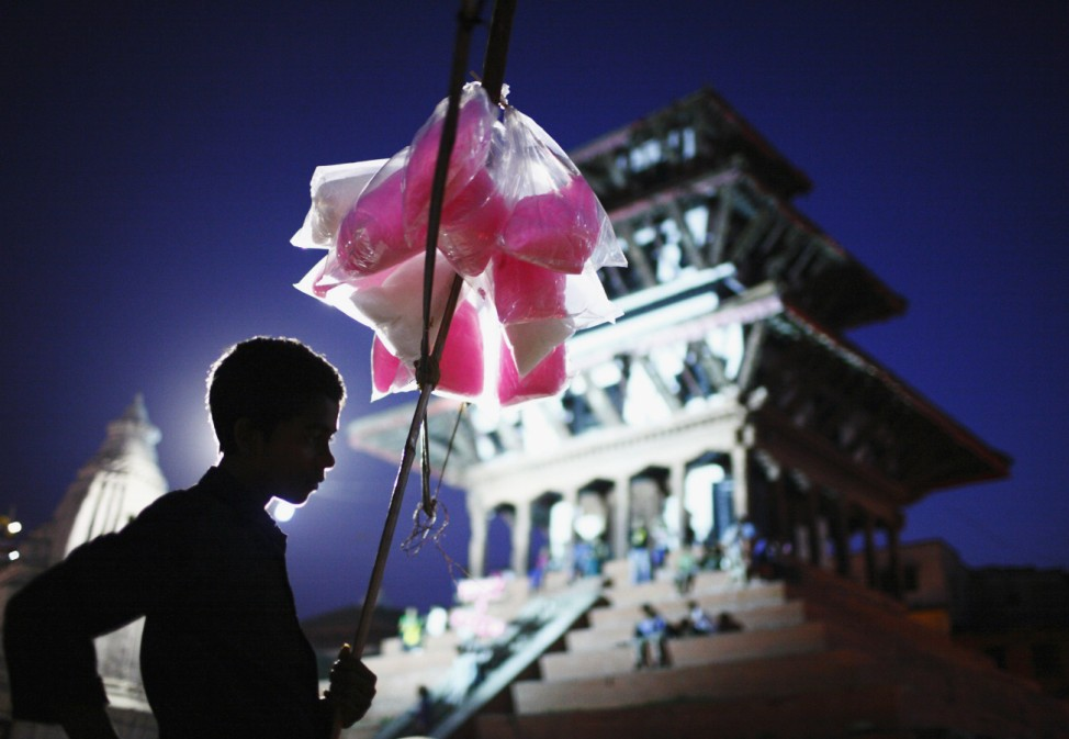 A boy selling cotton candy waits for customers on the streets of Kathmandu