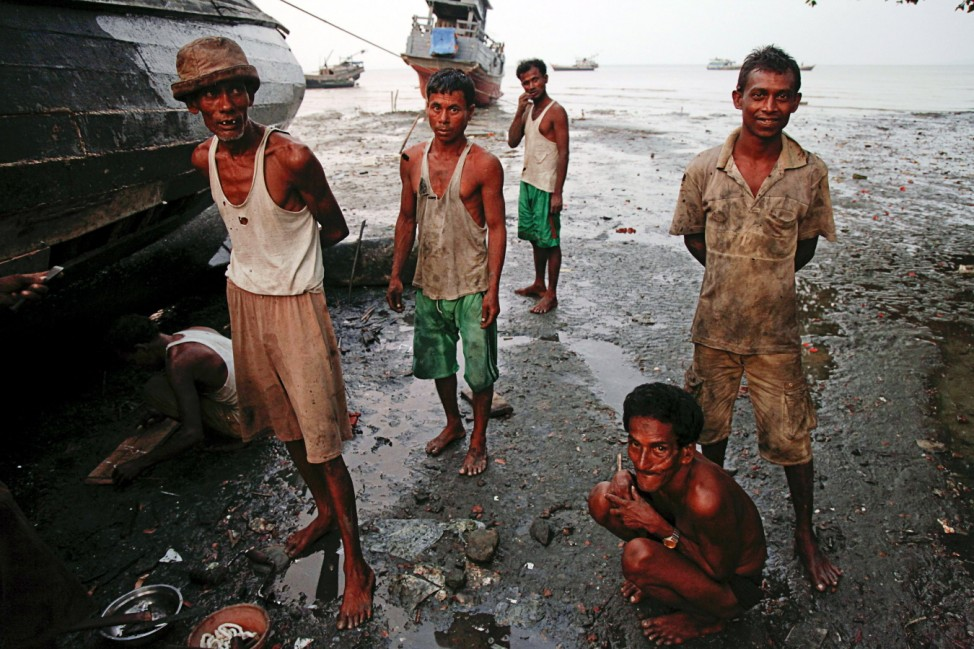 Myanmar Rohingya fishermen pause from repairing their boat at the slum near the sea in the town of Sittwe at sunset