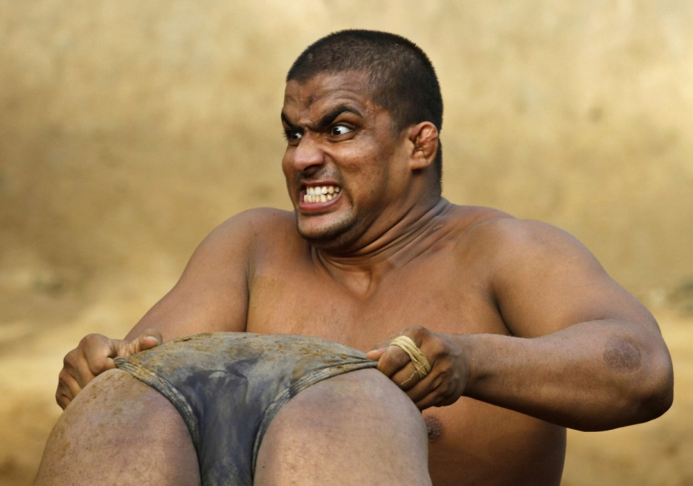 A wrestler reacts as he lifts his colleague at a mud wrestling centre in Noida