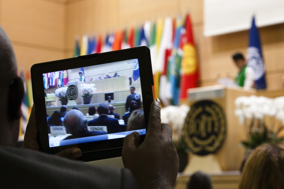 A delegate films Myanmar's pro-democracy leader Suu Kyi delivering a speech during the last day of the 101st session of the International Labour Conference in Geneva