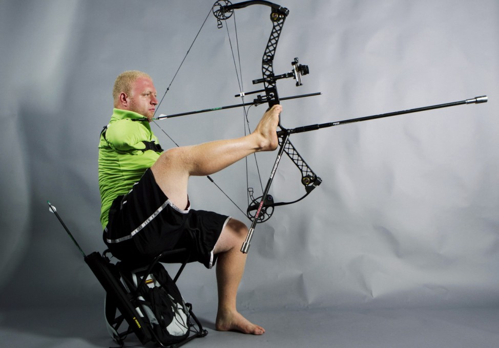 Paralympic archer Matt Stutzman uses his feet to hold and aim his bow while demonstrating his archery technique in New York