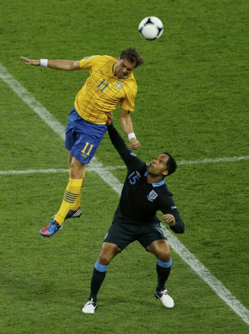 England's Lescott looks on as Sweden's Elmander jumps for the ball during their Group D Euro 2012 soccer match at Olympic stadium in Kiev