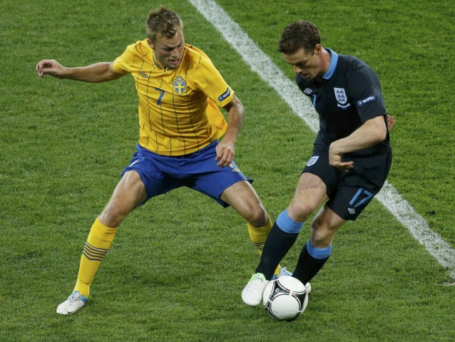 England's Scott Parker is challenged by Sweden's Sebastian Larsson during their Group D Euro 2012 soccer match at the Olympic stadium in Kiev