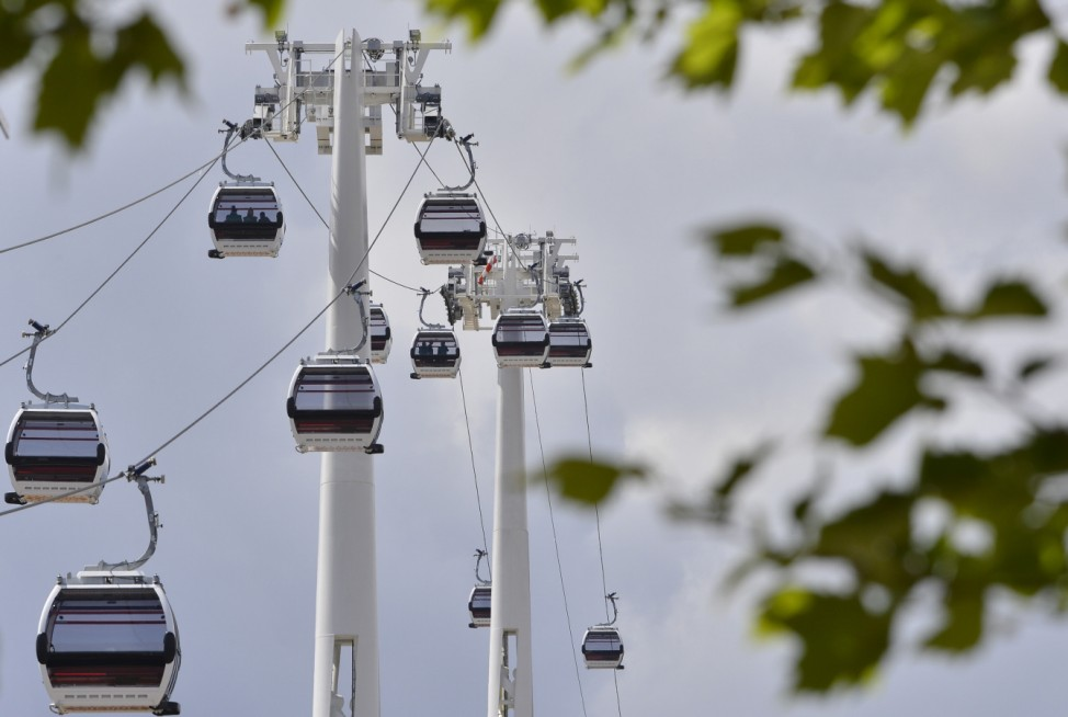 Workers sit in gondolas as they perform tests on the new cable car link across the River Thames in London