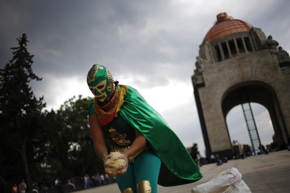 A demonstrator spreads sawdust to form a large 'G20' word on the floor, during a protest against the G20 Summit in Mexico City