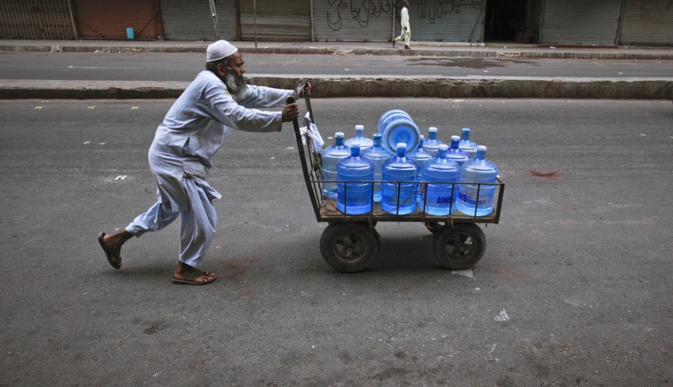 A man pushes a cart carrying water bottles which he supplies to a nearby market in the early morning in Karachi