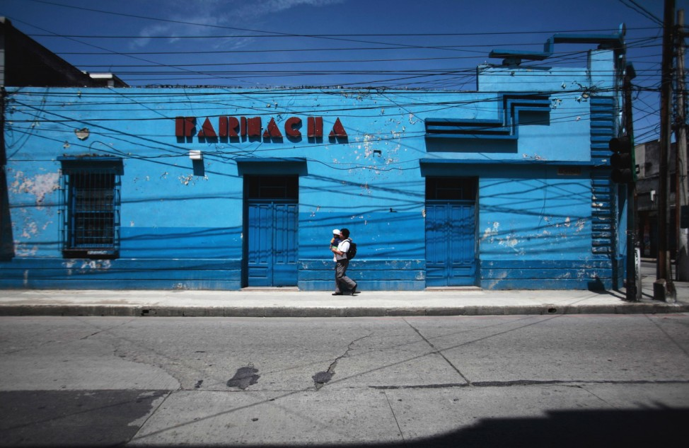 A man carries a baby while walking on the streets of Guatemala City