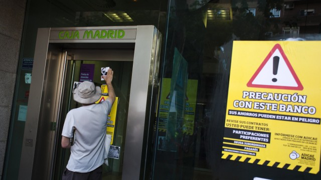 Protester sticks sign on entrance of Bankia-Caja Madrid bank branch next to yellow banner during demonstration against Spain's bailout in Madrid