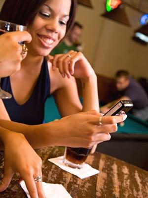 Frau in Bar mit Handy