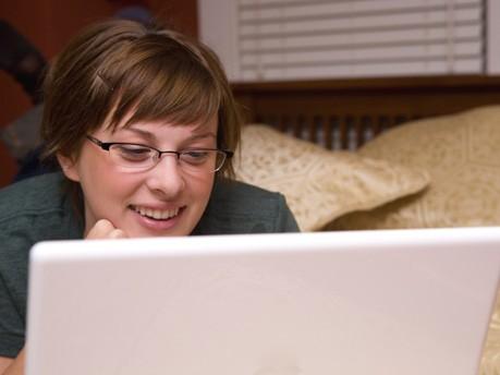 Frau mit Computer auf Bett