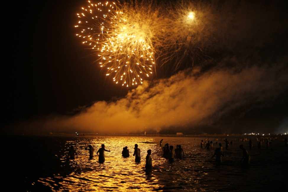People watch fireworks as they take a bath in the Mediterranean Sea on San Juan's night in Malaga