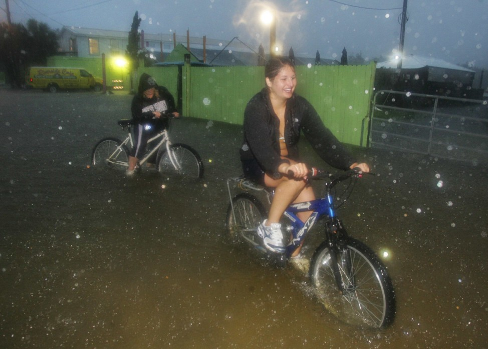 Bicyclists try to navigate a foot of water covering Riverside Drive in St. Marks