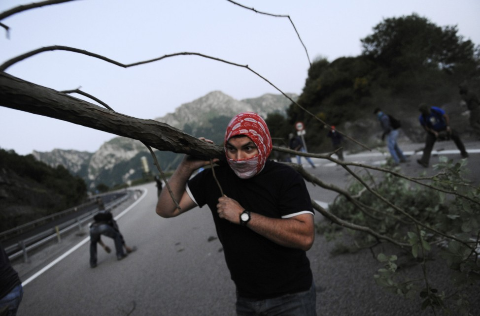 A coal miner carries a tree trunk to make a barricade on motorway AP-66, between Asturias and Leon, during a protest in Pola de Lena