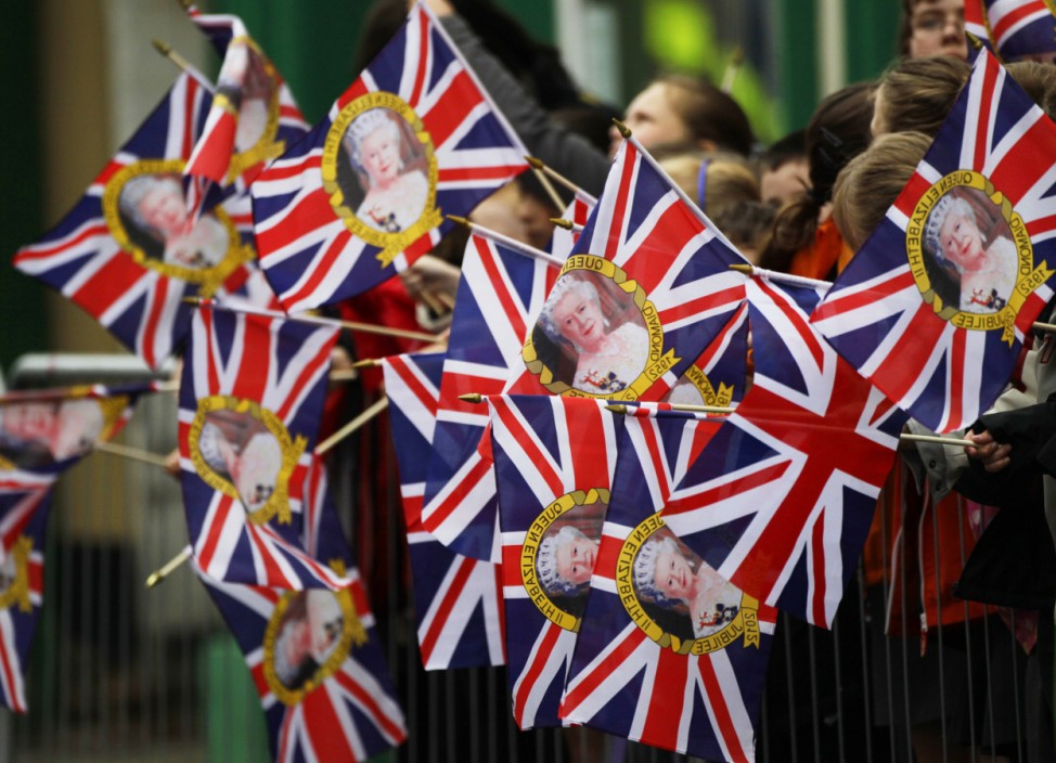 Schoolchildren wave union flags as they wait for Britain's Queen Elizabeth and Prince Philip to arrive at Saint Macartin's Cathedral in Enniskillen, Northern Ireland