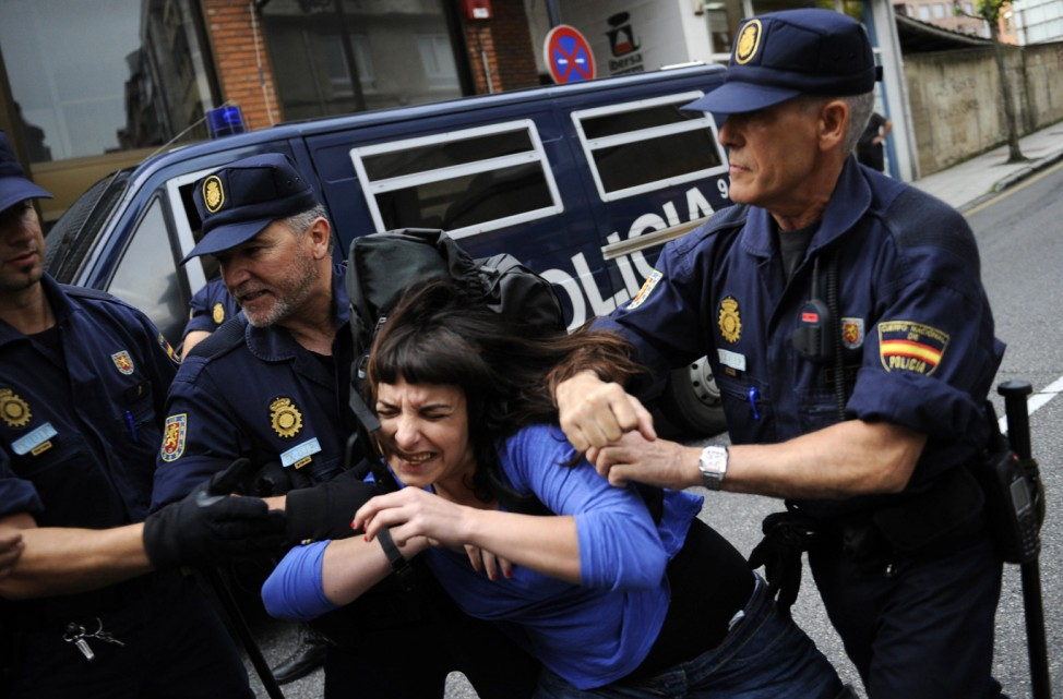 Riot police try to arrest a member of the 'Stop Deshaucios' social movement during a protest to prevent an eviction in Oviedo