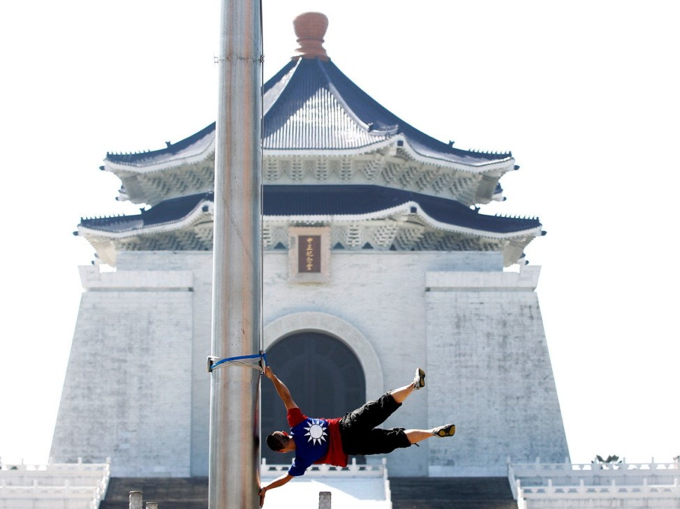 Cyclist Liao Hong-lin, 29, who nicknamed himself the 'Taiwan Floatman', poses for photographer in front of Taiwan's landmark, Chiang Kai-shek Memorial Hall, in Taipei