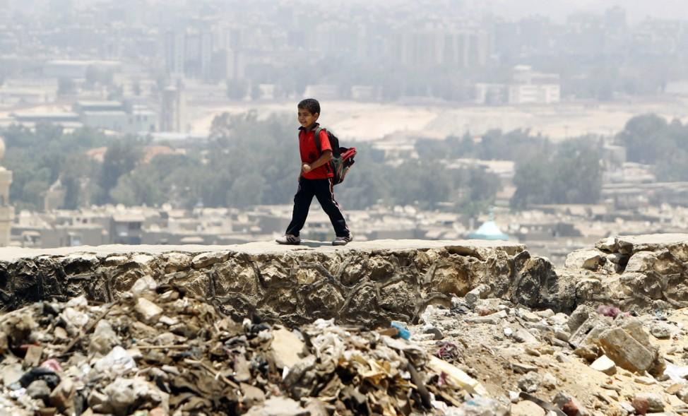 An Egyptian boy walks on a wall on a mountain near Manshiyet Nasser shanty town in eastern Cairo