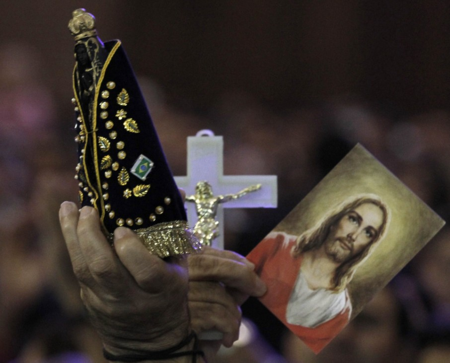 Pilgrim holds a statue of Our Lady of Aparecida and a picture of Christ during a mass at the Basilica of Our Lady of Aparecida, in the city of Aparecida