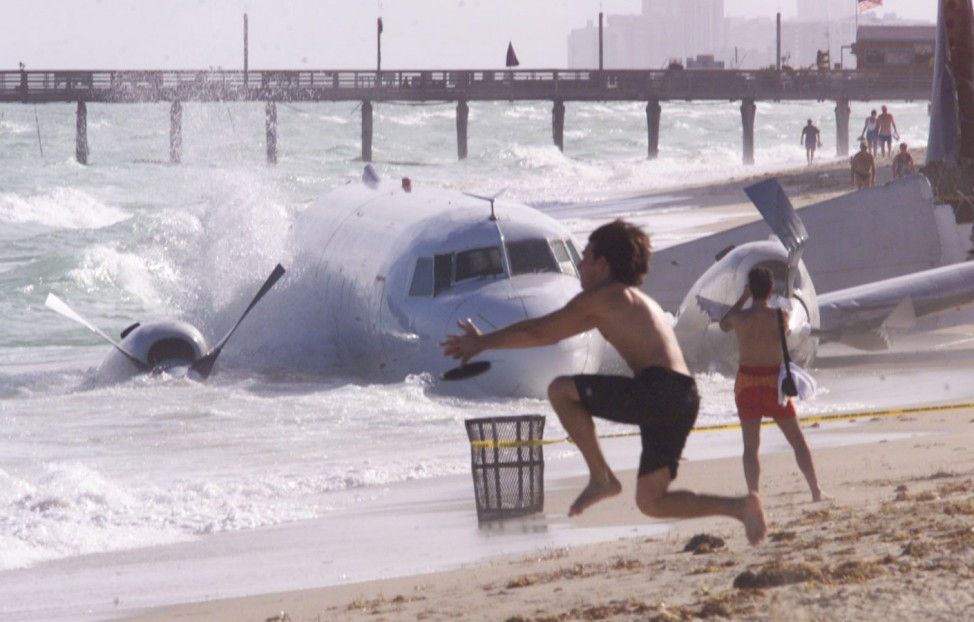 TOURISTS PLAY ON BEACH AS TRANS AIR CARGO PLANE RESTS IN THE SURF ALONG NORTH MIAMI BEACH