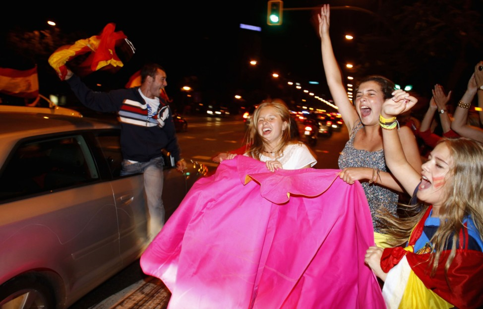 Spain's soccer fans celebrate Spain's victory over Italy in their Euro 2012 final soccer match held in Kiev, along a street in Madrid